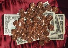 美元纸币和硬币,在红色天鹅绒背景的美国 免版税库存图片