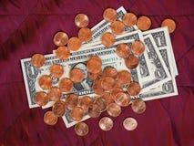 美元纸币和硬币,在红色天鹅绒背景的美国 库存图片