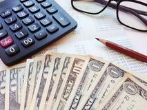 美元金钱、计算器和储蓄存款书或者财政决算在办公室桌上 免版税库存图片