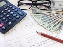 美元金钱、计算器和储蓄存款书或者财政决算在办公室桌上 库存照片
