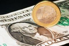 美元钞票和一枚欧洲硬币 免版税库存图片