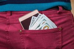 美元,在牛仔裤的现代智能手机装在口袋里 库存图片