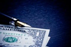 美元临近在老木头的金黄钢笔 免版税库存照片