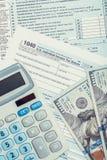 美利坚合众国与计算器的报税表1040和在它的美元-接近的演播室射击 免版税图库摄影