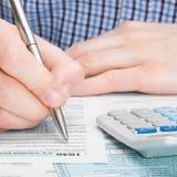 美利坚合众国报税表1040 -填好报税表的男性-一对一比率 图库摄影