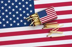 美利坚合众国旗子在一个开放火柴盒显示,几次比赛落和在一面大旗子的谎言 免版税库存图片