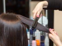 美发师与头发铁对一个女孩,浅黑肤色的男人排列头发 免版税库存照片