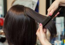 美发师与头发铁对一个女孩,美容院的浅黑肤色的男人排列头发 库存照片