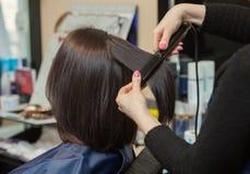 美发师与头发铁排列头发对一个女孩 库存图片