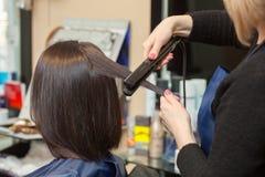 美发师与头发铁排列头发对一个女孩 免版税库存照片