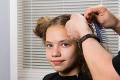 美发师做一个女孩的一种发型,有卷发的 免版税图库摄影