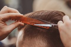 ?? 美发师做发型和样式剪刀和梳子 图库摄影