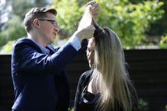 美发师做她的头发 免版税库存照片