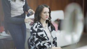 美发师做最后阶段创造一个逗人喜爱的女孩的一种发型 专业美发师美发师做a 影视素材