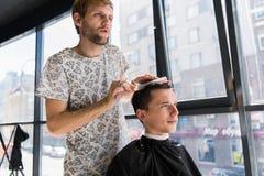 美发师做有英俊的满意的客户梳子的头发专业理发沙龙的 免版税图库摄影