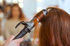 美发师做有长的红色头发的发型女孩在美容院 库存图片
