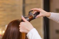 美发师做有长的红色头发的发型女孩在美容院 免版税库存图片