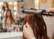美发师做有长的红色头发的发型女孩在美容院 图库摄影