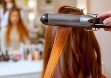 美发师做有长的红色头发的发型女孩在美容院 库存照片