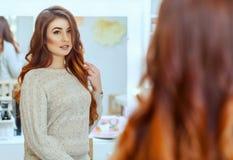 美发师做有长的红色头发的发型女孩在美容院 免版税图库摄影