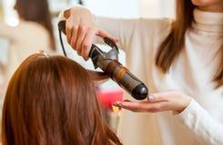 美发师做有长的红色头发的发型女孩在美容院 用烫发钳创造卷毛 库存照片