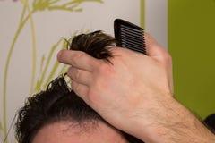 美发师做有黑梳子的头发在专业理发沙龙 免版税库存照片