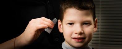美发师做男孩的一种发型有在他的面孔的微笑的 免版税库存照片