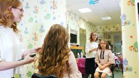美发师做称呼与小逗人喜爱的女孩的喷发剂 对镜子的Backview 影视素材