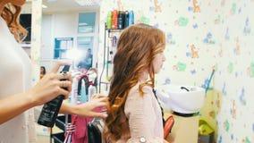 美发师做称呼与小逗人喜爱的女孩的喷发剂 影视素材