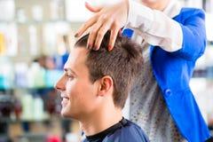 美发师切口人头发在理发店 免版税库存照片
