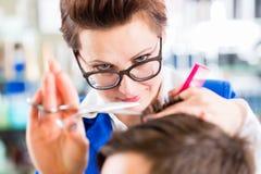 美发师切口人头发在理发店 免版税库存图片
