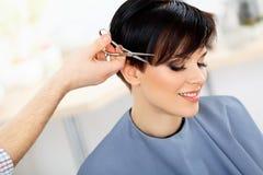 美发师切口在美容院的妇女的头发。理发 图库摄影