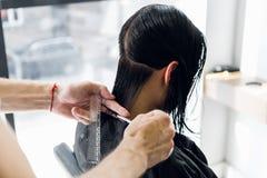 美发师切口客户在沙龙的` s头发与剪刀特写镜头 使用梳子 免版税库存图片