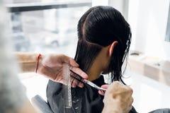 美发师切口客户在沙龙的` s头发与剪刀特写镜头 使用梳子 库存图片