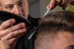 美发师切口有电头发剪刀的客户头发 免版税库存照片