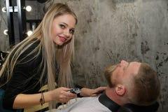 美发师切开在美发店的客户的胡子 库存照片