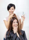 美发师剪女孩的头发美发师的 免版税库存图片