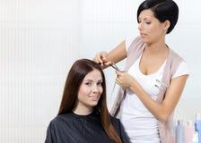 美发师剪妇女的头发美发师的 免版税库存照片