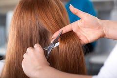 美发师剪顾客头发 免版税库存照片