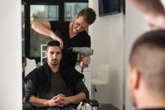 美发师吹干人的头发在商店 免版税库存图片