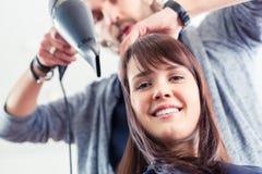 美发师吹干头发在商店 免版税库存照片