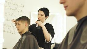 美发师喷洒的水和梳在切开前的湿头发 在理发师沙龙的男性发型 妇女理发师梳 影视素材