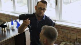 美发师固定与吹风器的发型 有一个胡子的可敬的灰发的人在客户的椅子 股票录像