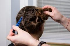 美发师在他的手上拿着一个发夹并且做孩子的一种发型 库存照片