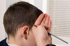 美发师在他的手上拿着一把梳子并且做男孩的一种发型 图库摄影