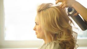 美发师在女商人的金发做晚上发型特写镜头美容院的 股票视频