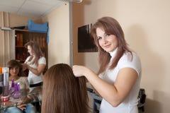 美发师在妇女头发工作 免版税库存照片