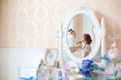 美发师在婚礼之日做构成新娘 免版税库存照片