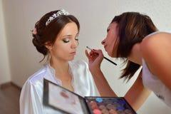美发师在婚礼之日做构成新娘 免版税库存图片