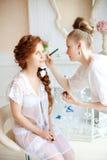 美发师在婚礼前做构成新娘 库存照片
